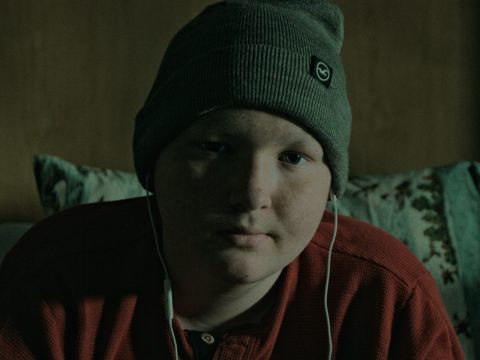 Boy sitting on hospital bed listening to music through ear buds