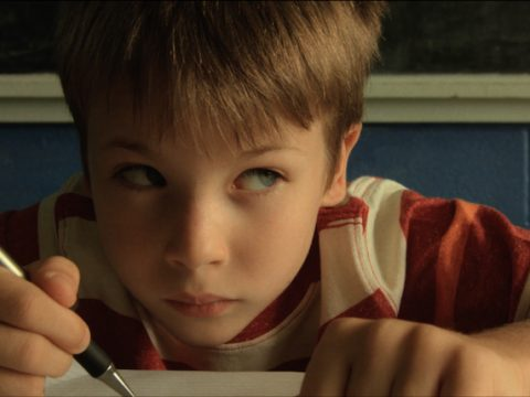 Boy looking up from writing at desk