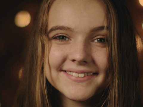 girl smiling in the glow of golden lights